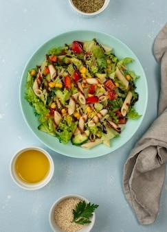 Bovenaanzicht pastasalade met balsamicoazijn, sesamzaadjes en olie