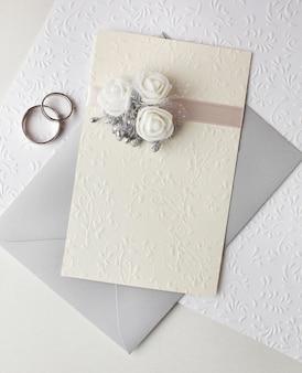 Bovenaanzicht pastelkleurige huwelijksuitnodigingen en ringen