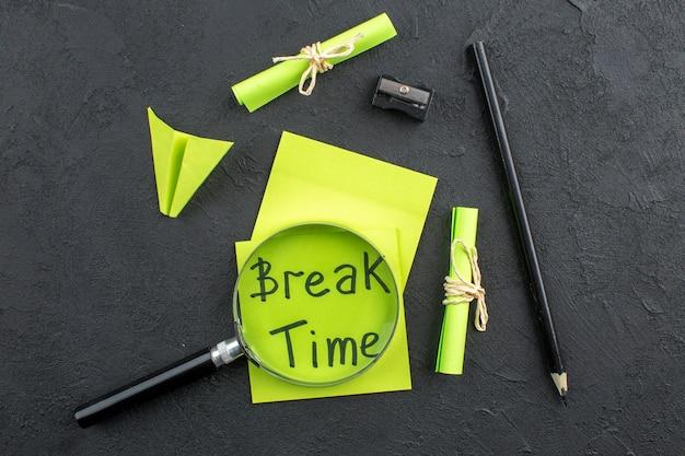 Bovenaanzicht pauze geschreven op gele plaknotities papier vliegtuig zwart potlood lupa puntenslijper opgerolde notities vastgebonden met touw op donkere muur