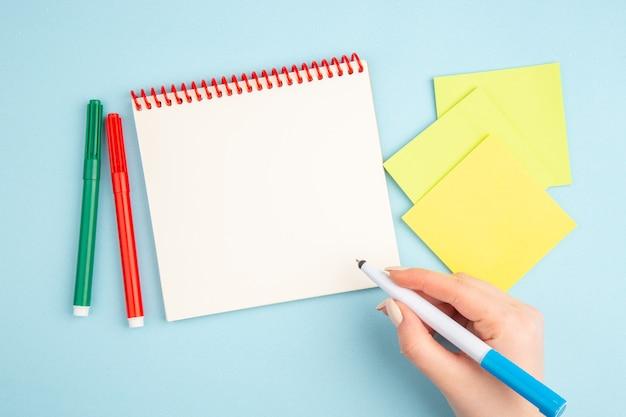 Bovenaanzicht pen in de hand gele kleverige papieren markeringen notitieblok op blauw
