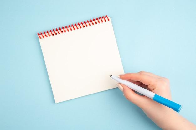 Bovenaanzicht pen in de hand notitieblok op blauw