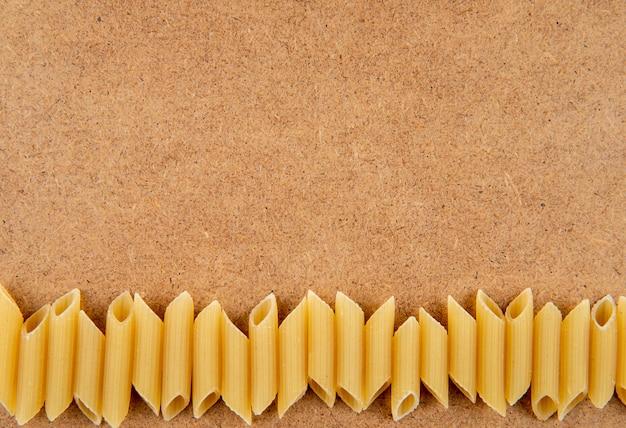Bovenaanzicht penne pasta op de bodem met kopie ruimte op bruine achtergrond