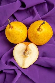 Bovenaanzicht peren en een halve peer twee peren en een halve peer op het tafelkleed op tafel Gratis Foto