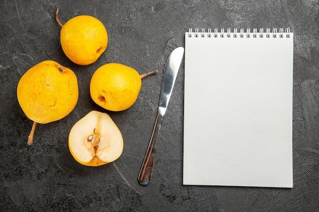Bovenaanzicht peren en mes drie peren mes en een halve peer naast het witte notitieboekje op de zwarte tafel