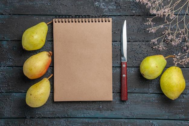 Bovenaanzicht peren en notitieboekje crème notitieboekje en mes tussen smakelijke peren naast boomtakken