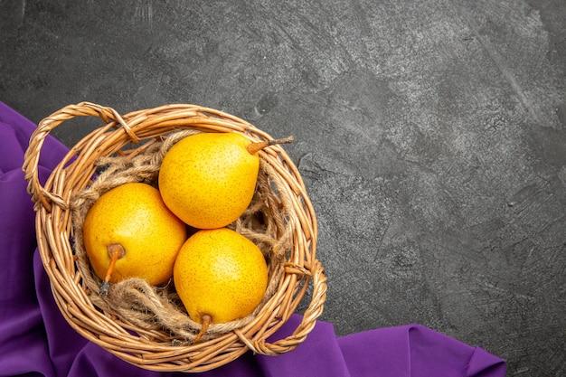 Bovenaanzicht peren in mandmand met drie rijpe peren op het paarse tafelkleed op de donkere tafel