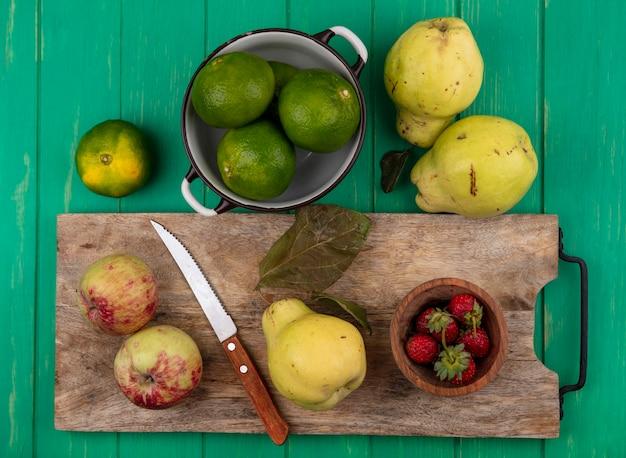 Bovenaanzicht peren met appels, mandarijnen en aardbeien op een snijplank