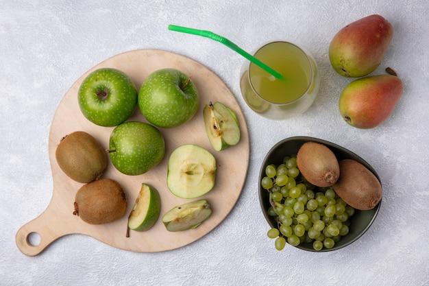 Bovenaanzicht peren met kiwi en druiven in een kom met groene appelschijfjes op een stand met appelsap op een witte achtergrond