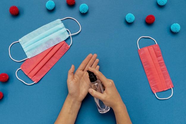 Bovenaanzicht persoon handen desinfecteren in de buurt van kleurrijke medische maskers