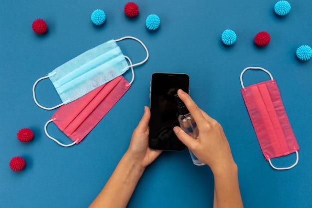 Bovenaanzicht persoon met behulp van lege telefoon in de buurt van medische maskers