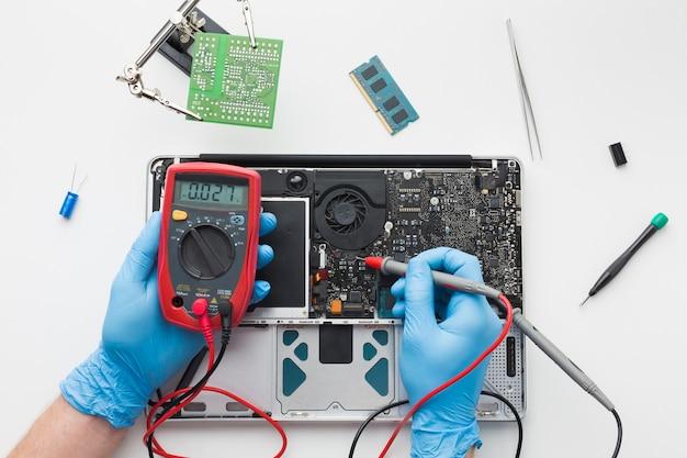 Bovenaanzicht persoon repareren van een laptop