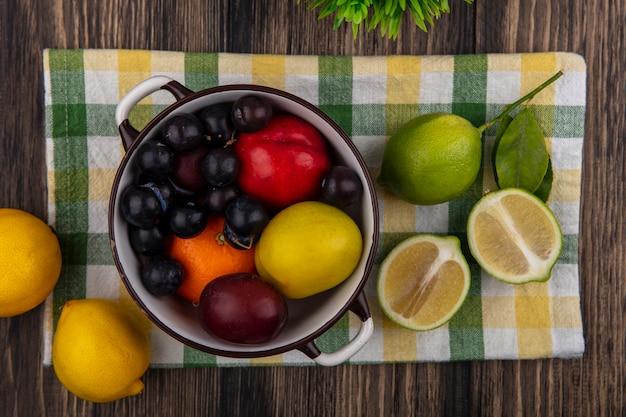Bovenaanzicht perzik met oranje pruim en kersenpruim in een pan met limoenen en citroenen op een geruite handdoek op een houten achtergrond