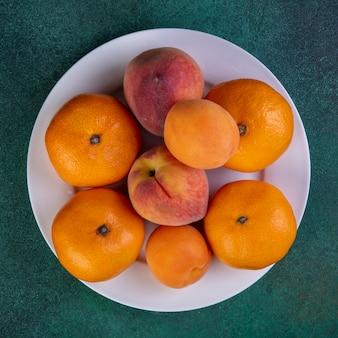 Bovenaanzicht perziken met mandarijnen en abrikozen op plaat op groen
