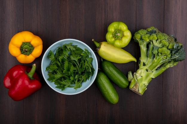 Bovenaanzicht peterselie in een kom met broccoli, komkommer en paprika op een houten achtergrond