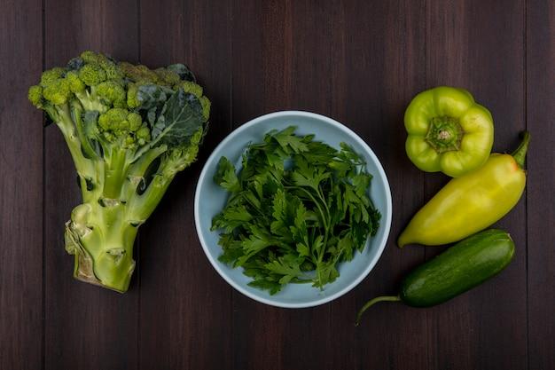 Bovenaanzicht peterselie in kom met broccoli, komkommer en paprika op houten achtergrond