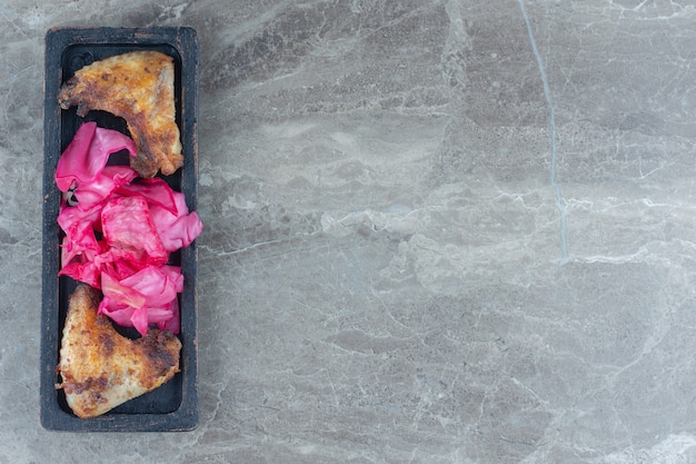 Bovenaanzicht pf gegrilde kippenvleugel en zuurkool op een houten bord. Gratis Foto