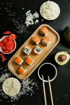 Bovenaanzicht philadelphia rolt op een standaard met gember-sojasaus avacado gekookte rijst en sesamzaadjes op een zwarte tafel
