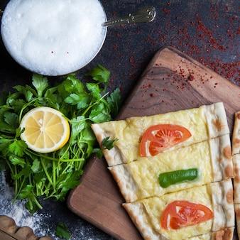 Bovenaanzicht pide met peterselie en citroen en kaas en ayran in snijplank