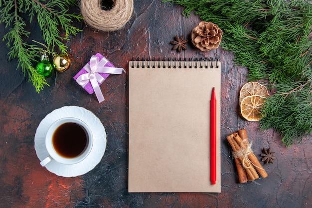 Bovenaanzicht pijnboomtakken en dennenappels een notebook rode pen anijs kaneel kopje thee op donkerrood oppervlak