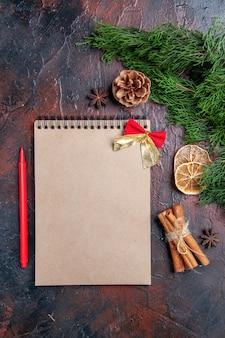 Bovenaanzicht pijnboomtakken en dennenappels een notebook rode pen anijs kaneel op donkerrood oppervlak