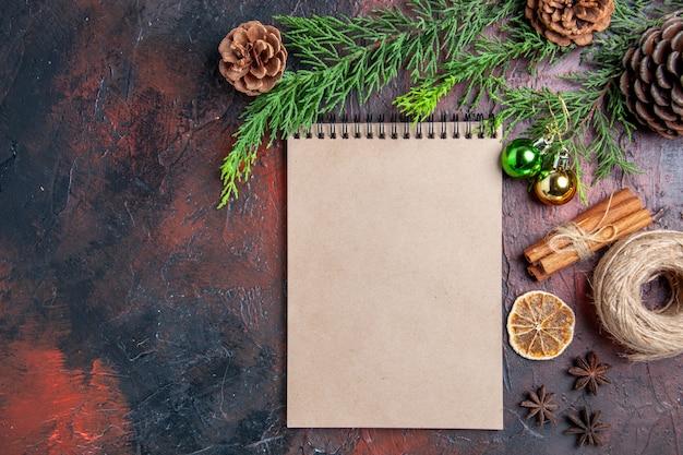 Bovenaanzicht pijnboomtakken en dennenappels een notitieboekje anijs kaneelstro draad op donkerrood oppervlak met vrije plaats