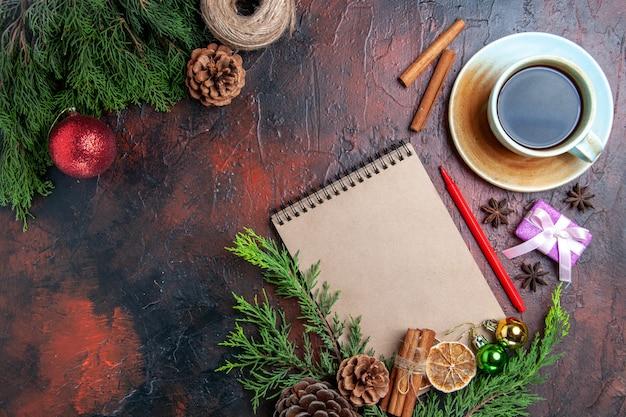 Bovenaanzicht pijnboomtakken en dennenappels een notitieboekje rode pen gedroogde plakjes citroen stro draad kopje thee anijs op donkerrood oppervlak met vrije plaats