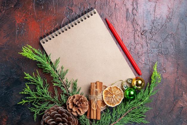 Bovenaanzicht pijnboomtakken en dennenappels op een notebook rode pen gedroogde citroen plakjes kaneelstokjes op donkerrode oppervlak vrije plaats