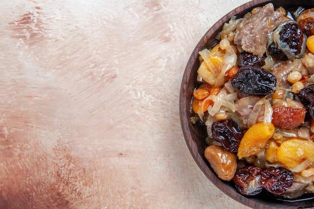 Bovenaanzicht pilaf pilaf met kastanjes gedroogd fruit in de kom op tafel
