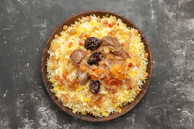 Bovenaanzicht pilaf pilaf met vlees, gedroogd fruit en rozijnen in de kom