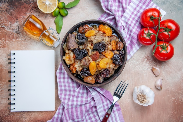 Bovenaanzicht pilaf pilaf op het tafellaken tomaten knoflook citroen olie vork wit notebook