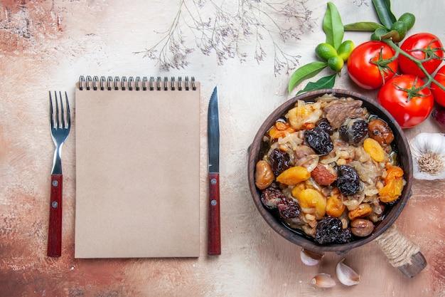 Bovenaanzicht pilaf tomaten knoflook kom pilaf op het bord vork mes crème notebook