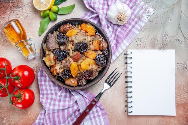 Bovenaanzicht pilaf witte notebook tomaten knoflook citroen olie vork pilaf op het tafellaken