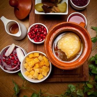 Bovenaanzicht piti met crackers en granaatappelpitjes en azijn in klei kruik