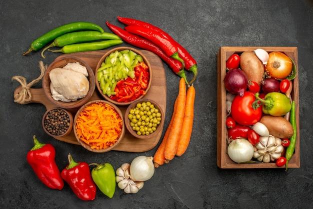 Bovenaanzicht pittige paprika's met bonen, kip en wortel op de donkere salade van de bureaukleur, vers rijp