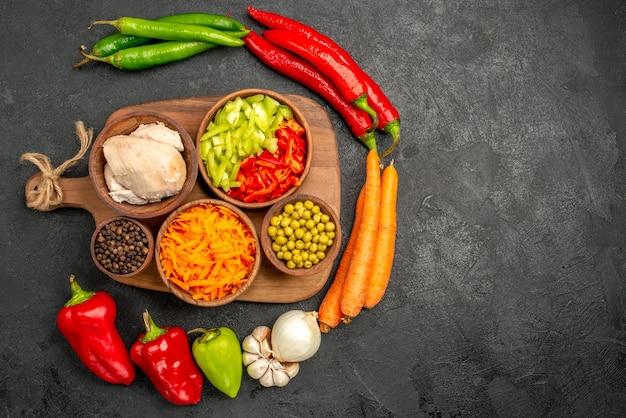 Bovenaanzicht pittige paprika's met bonen, kip en wortel op donkere tafel kleur salade rijp vers