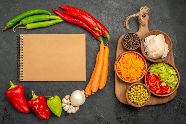 Bovenaanzicht pittige paprika's met bonen, kip en wortel op donkere vloer kleur salade rijp vers