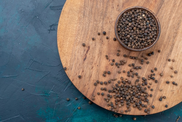 Bovenaanzicht pittige peper verspreid over donkerblauwe backgruond zout peper kruiden bureau