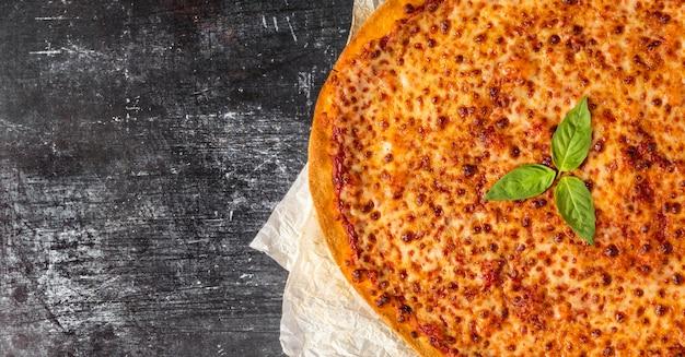 Bovenaanzicht pizza met kaas en basilicum met kopie-ruimte