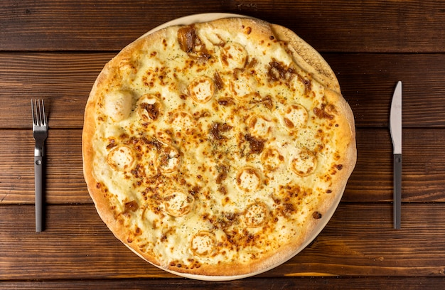 Bovenaanzicht pizza met kaas en bestek