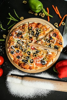Bovenaanzicht pizza met olijven, tomaten, paprika en deegroller met bloem
