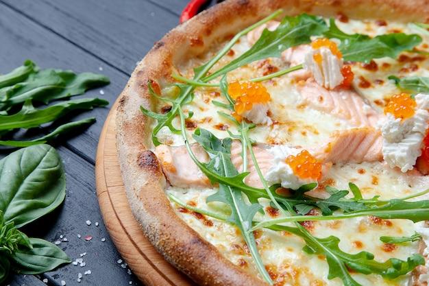 Bovenaanzicht pizza met zalm, rucola, rode kaviaar, kaas op donkere houten achtergrond met kopie sapce. italiaanse pizza met zeevruchten. voedsel achtergrond. lekkere zelfgemaakte italiaanse pizza