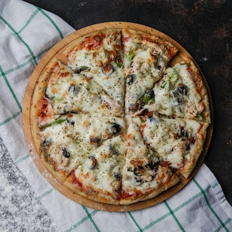 Bovenaanzicht pizza op een houten standaard met een tafellaken