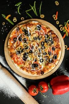 Bovenaanzicht pizza op een stand met tomaten, olijven en paprika op zwarte tafel