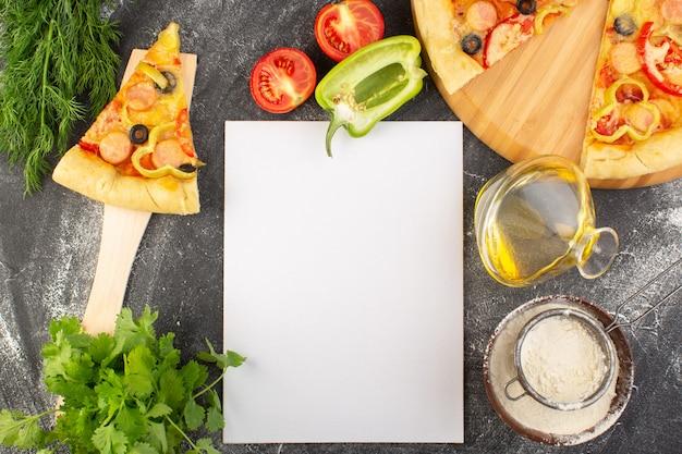 Bovenaanzicht pizzaplak met zwarte olijven, tomaten en worstjes, samen met groene olie en groenten op de grijze italiaanse het deegpizza van het bureauvoedsel