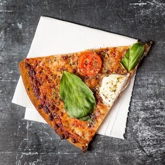 Bovenaanzicht pizzaplak op servet