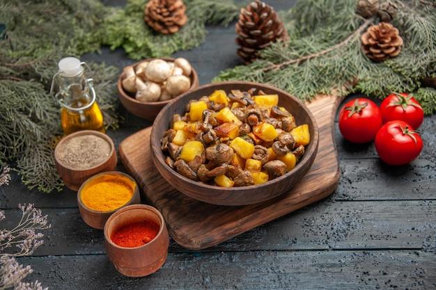 Bovenaanzicht plaat en groenten plaat van aardappelen en champignons op houten snijplank naast drie tomaten en verschillende kruiden onder olie in fles boomtakken en kom met champignons