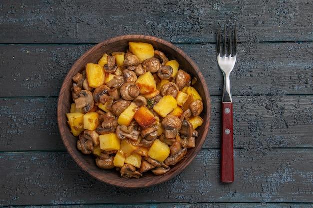 Bovenaanzicht plaat en vorkkom met smakelijke aardappelen en champignons naast de vork op donkere tafel