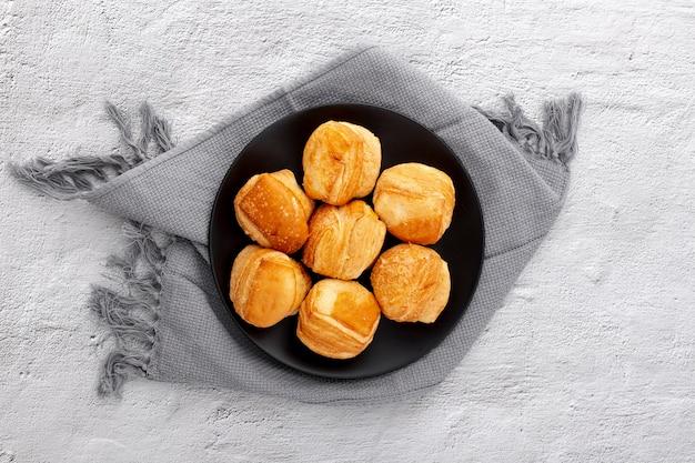 Bovenaanzicht plaat met gebakken broodjes en doek