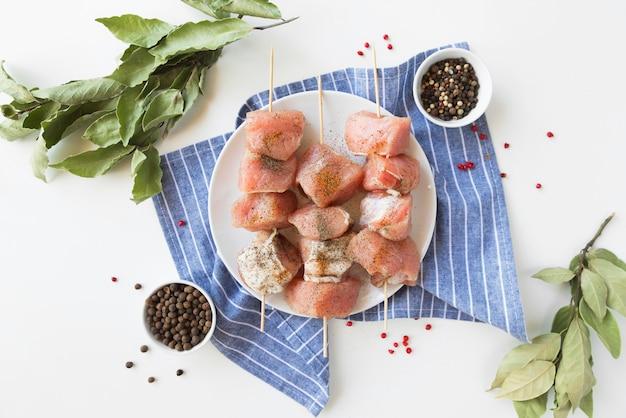 Bovenaanzicht plaat met spiesjes van rauw vlees