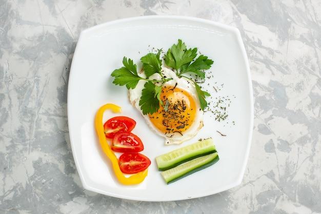 Bovenaanzicht plaat met voedsel groenten en greens op licht-wit bureau groenten eten maaltijd lunch kleurenfoto
